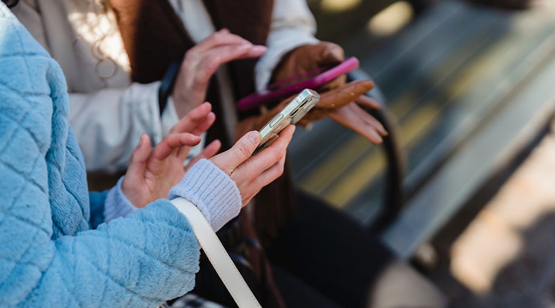 Two women checking their smartphones (SMS discounts)